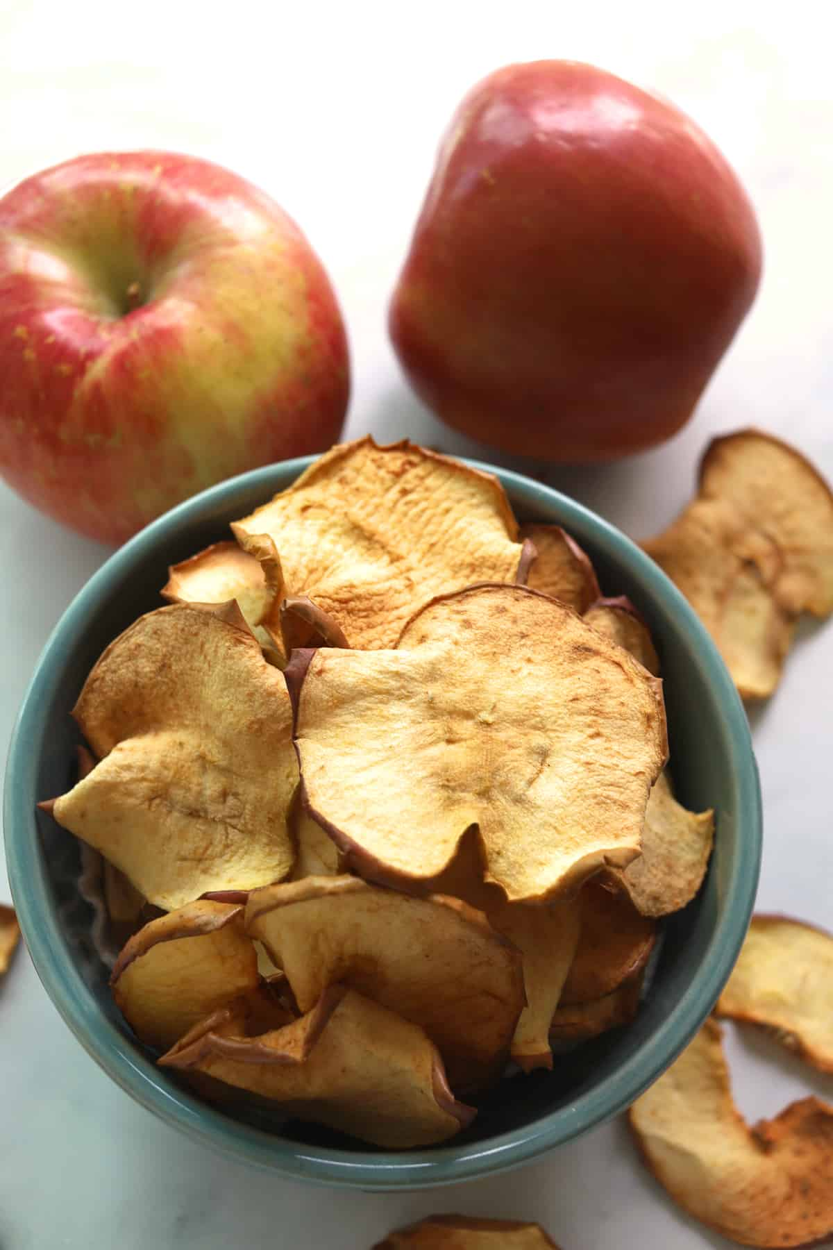 2 Apples in background with apple chips in a bowl.