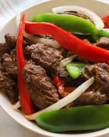 Plate with beef, sliced red and green bell peppers and white onions.