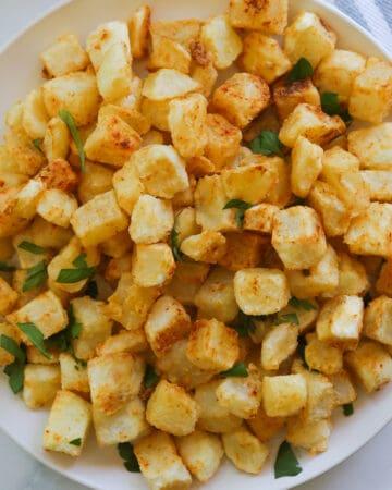 Plate of Closeup crispy cut potato squares.