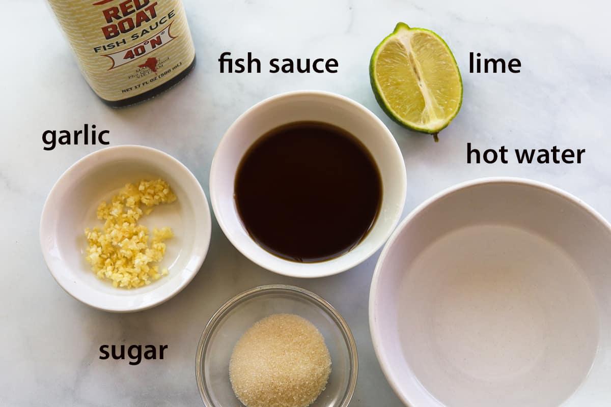 ingredients: fish sauce bottle, sauce in bowl, half lime, minced garlic, sugar, water in bowl