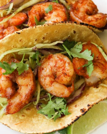 yellow tortilla with Shrimp on top of sliced purple and green cabbage. Garnished with cilantro.