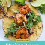 1 yellow tortilla with shrimp on top of sliced purple and green cabbage. Garnished with cilantro and lime wedges.