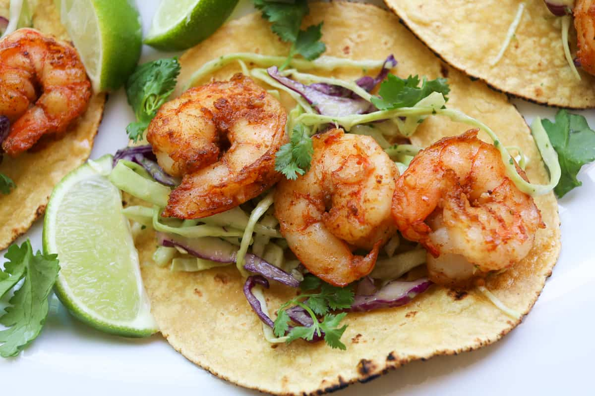 yellow tortillas with Shrimp on top of sliced purple and green cabbage garnished with cilantro and lime wedges.
