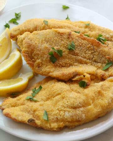 3 golden crusted fish fillets garnished with lemon wedges and parsley leaves.