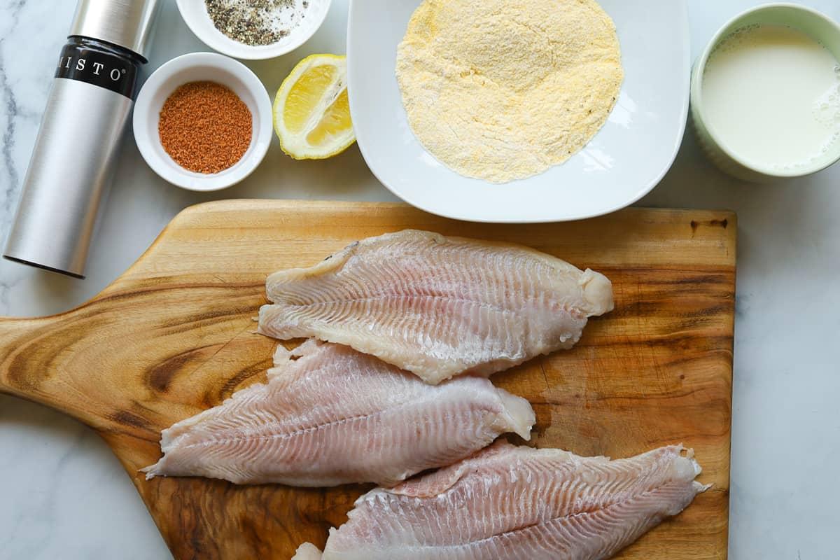 ingredients: 3 fish fillets, cajun seasoning, cornmeal mix, lemon, pepper