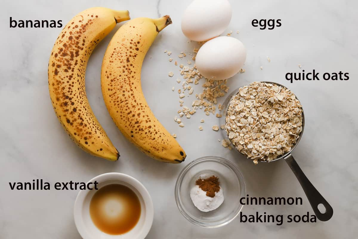Ingredients on table. Bananas, eggs, oats, vanilla extract in bowl, cinnamon and baking soda in bowl.