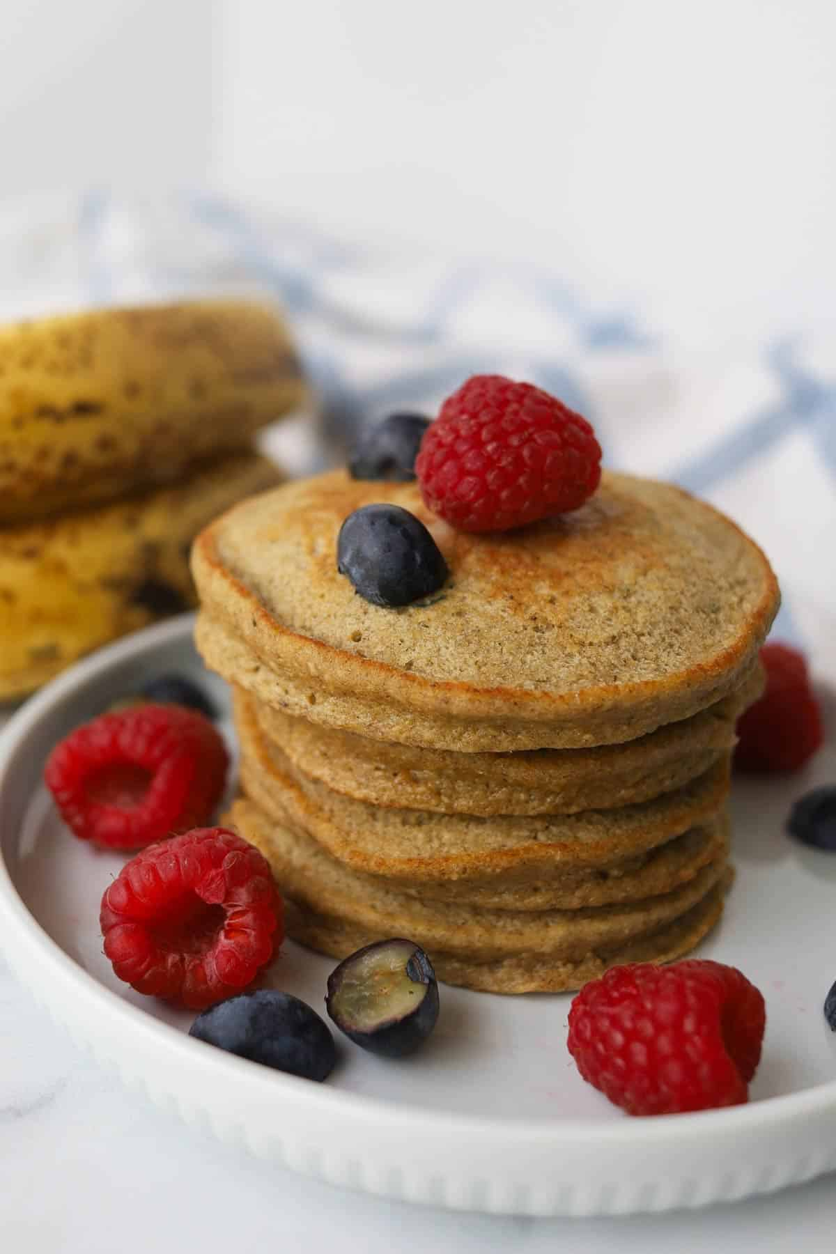 Stack of small pancakes garnished with raspberries and blueberries