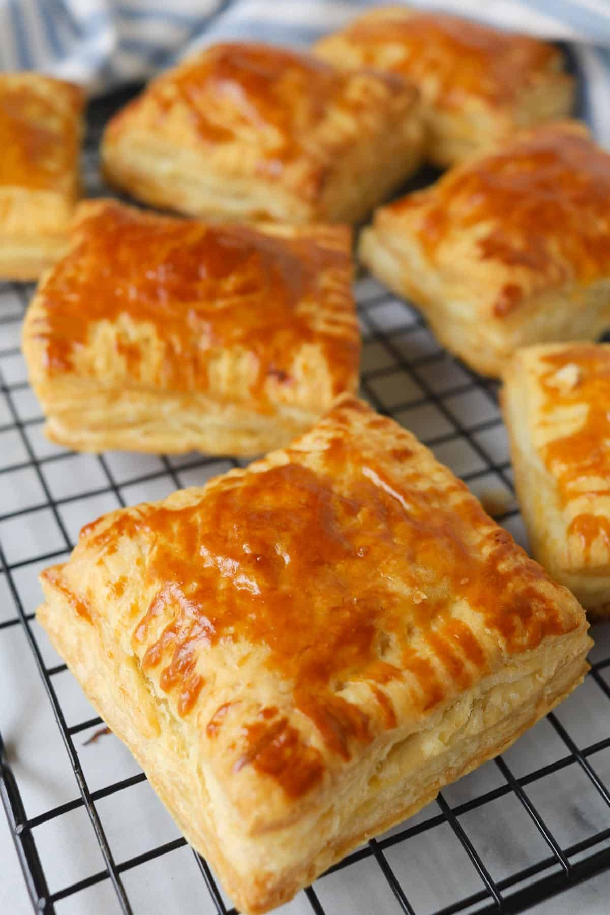 Golden square puff pastries on a cooling rack.