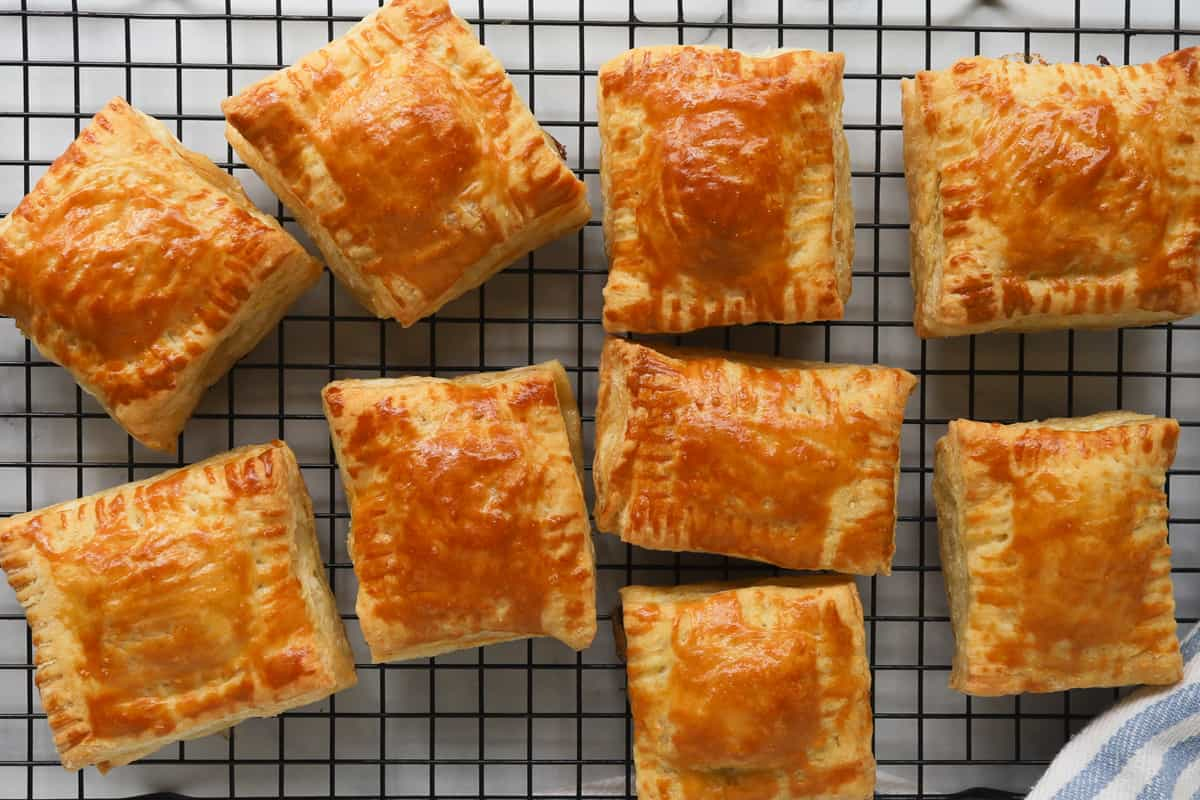Golden square puff pastries on a cooling rack
