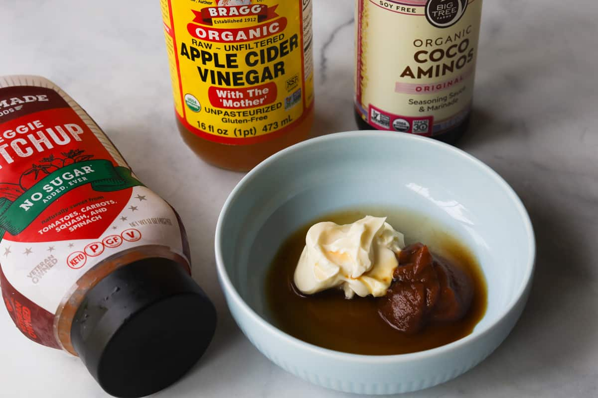 picture of bottle of ketchup, bottle apple cider vinegar and bottle of coco aminos. Small bowl with mayo, ketchup, coco aminos and apple cider vinegar.