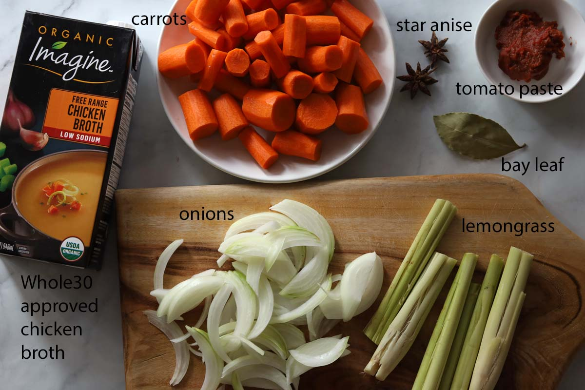 Ingredients picture of chicken broth carton, cut carrots, 2 star anise, tomato paste, one bay leaf, cut onions, lemongrassss
