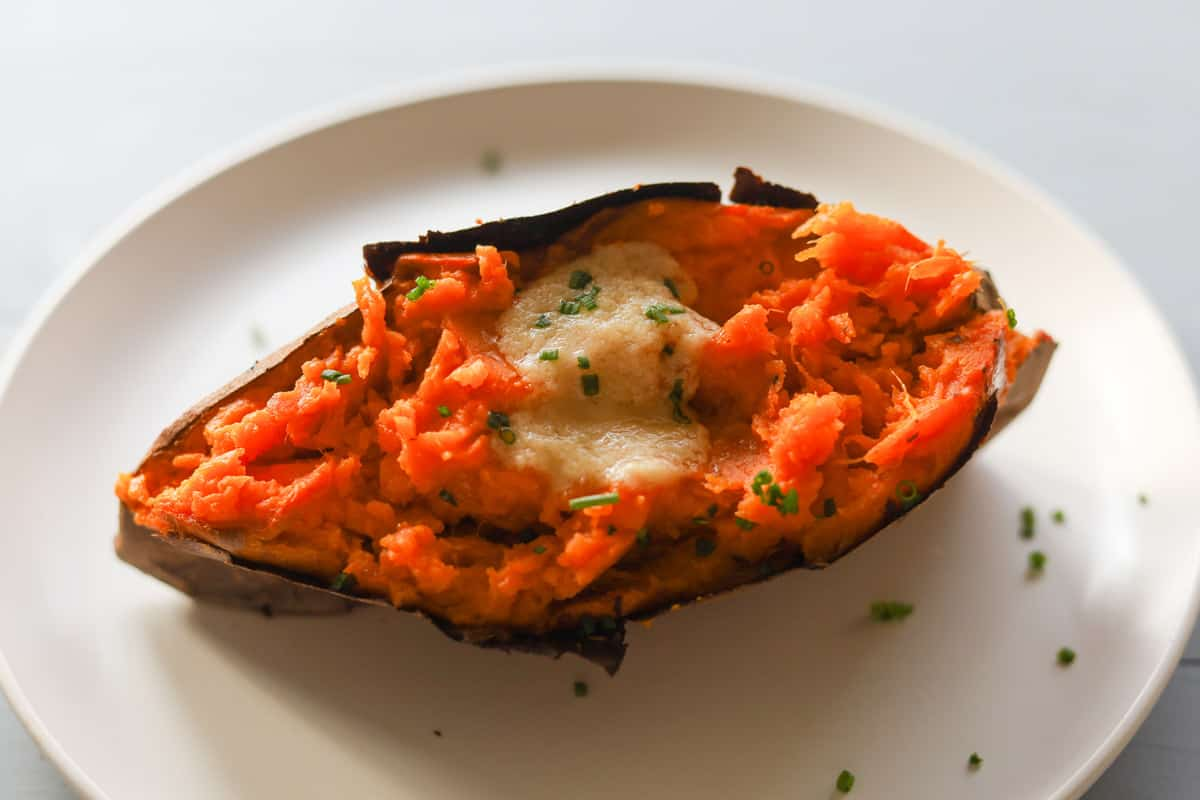 One roasted sweet potato cut open with melted butter and chives garnish.