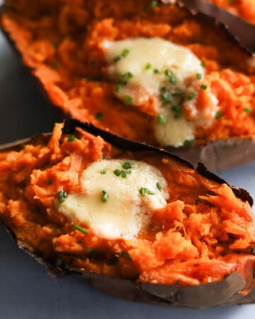 Closeup of roasted sweet potatoes garnished with melted butter and chives.