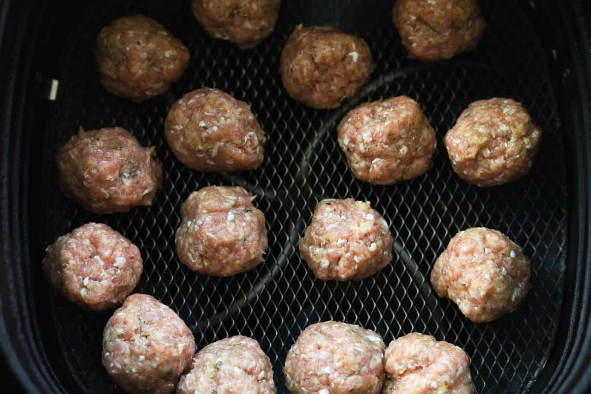 Uncooked meatballs in an air fryer basket.