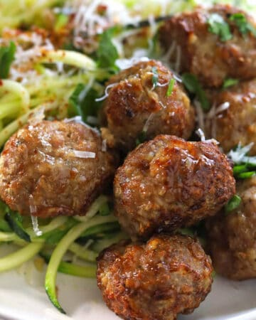 Golden brown meatballs with zucchini noodles garnished with grated cheese and chopped parsley.