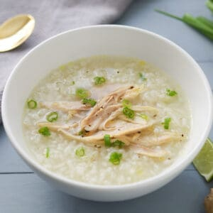 A bowl of rice porridge with shredded chicken, garnished with green onions.