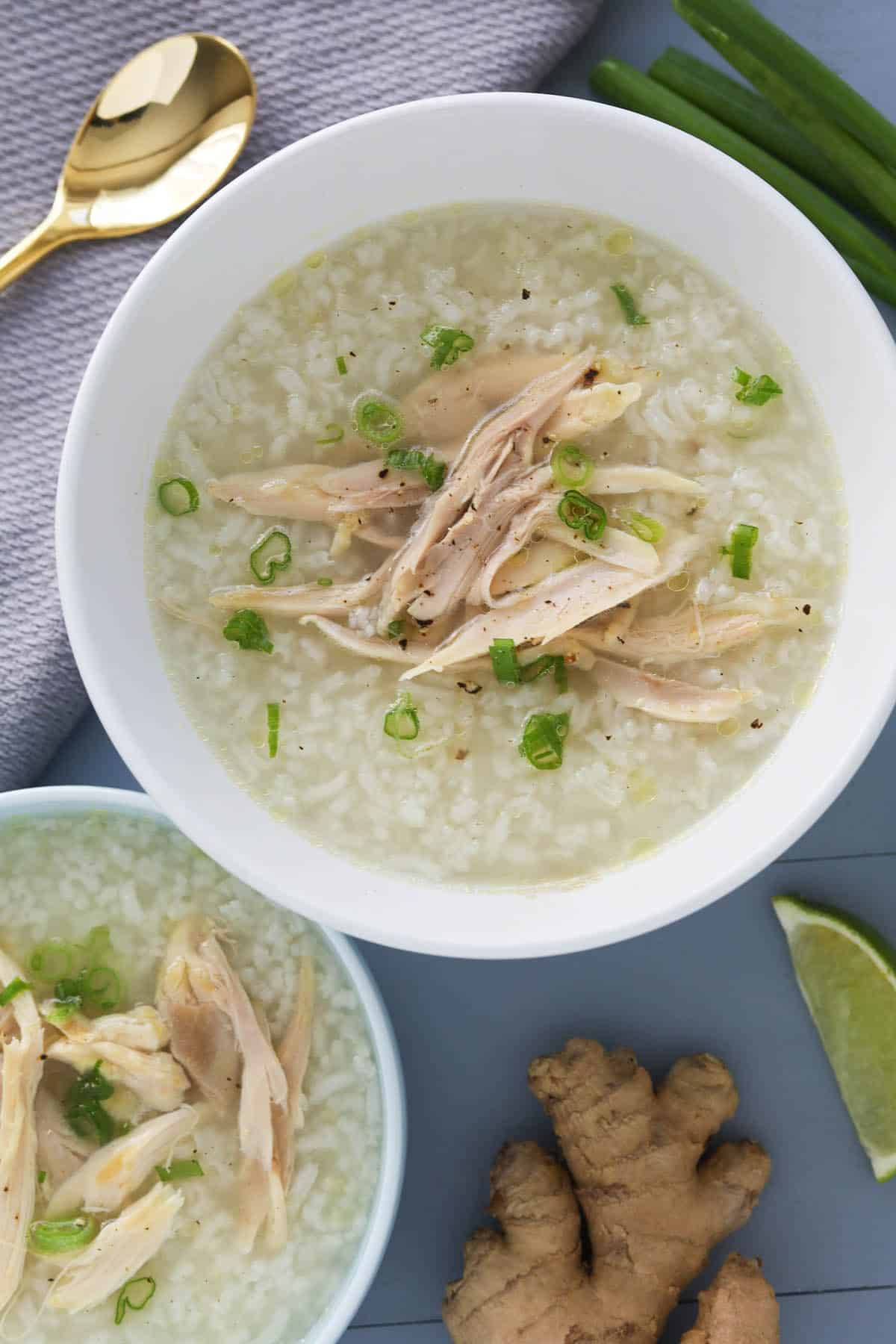 Two bowls of rice porridge with shredded chicken, garnished with green onions.