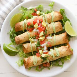 Four golden taquitos on top a bed of sliced lettuce, drizzled with avocado crema sauce and topped with diced tomatoes, cilantro, onions and avocado.