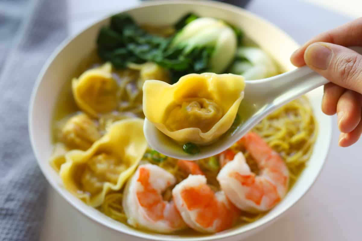 Closeup of spoon holding a single wonton. Background of bowl of wonton soup with noodles, shrimp, bokchoy and green onions.
