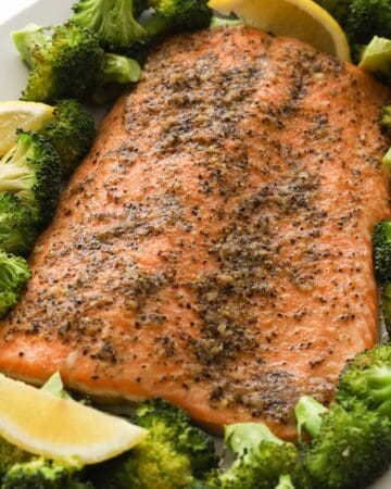 Closeup image of cooked salmon fillet with broccoli florets and lemon wedges on a plate.