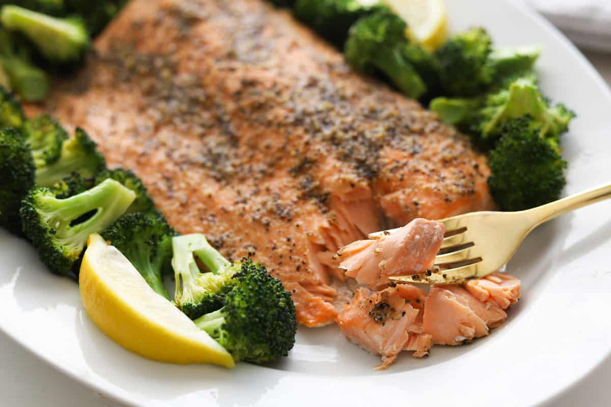 Cooked salmon fillet with broccoli and lemon wedges on a plate. Salmon flesh flaked with a fork.