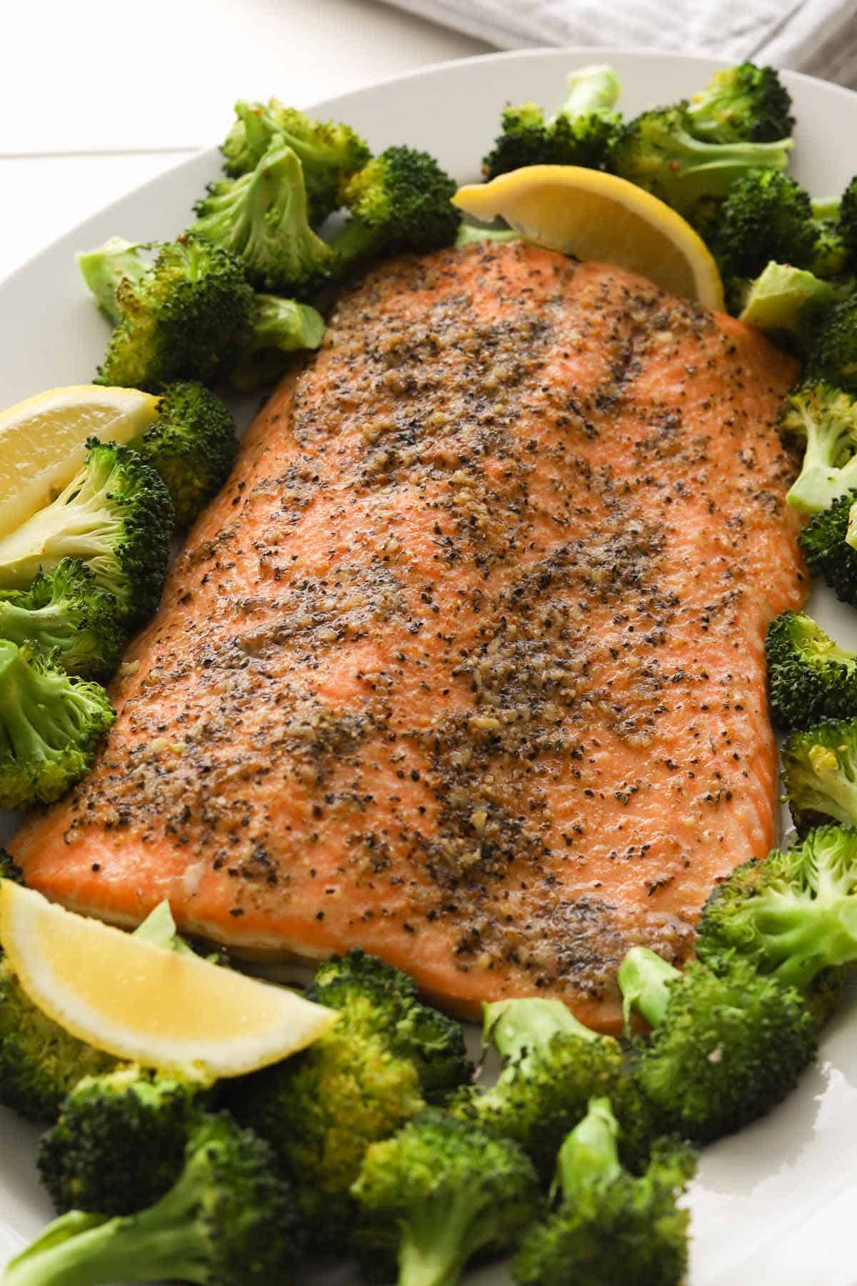 Cooked salmon fillet with broccoli florets and lemon wedges on a plate.