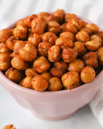 Close up image of roasted chickpeas with seasoning in a bowl.