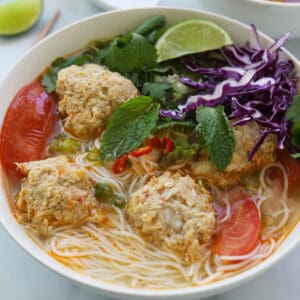 Bowl of rice noodles with soup, crab meatballs, tomatoes and garnished with fresh greens and herbs.
