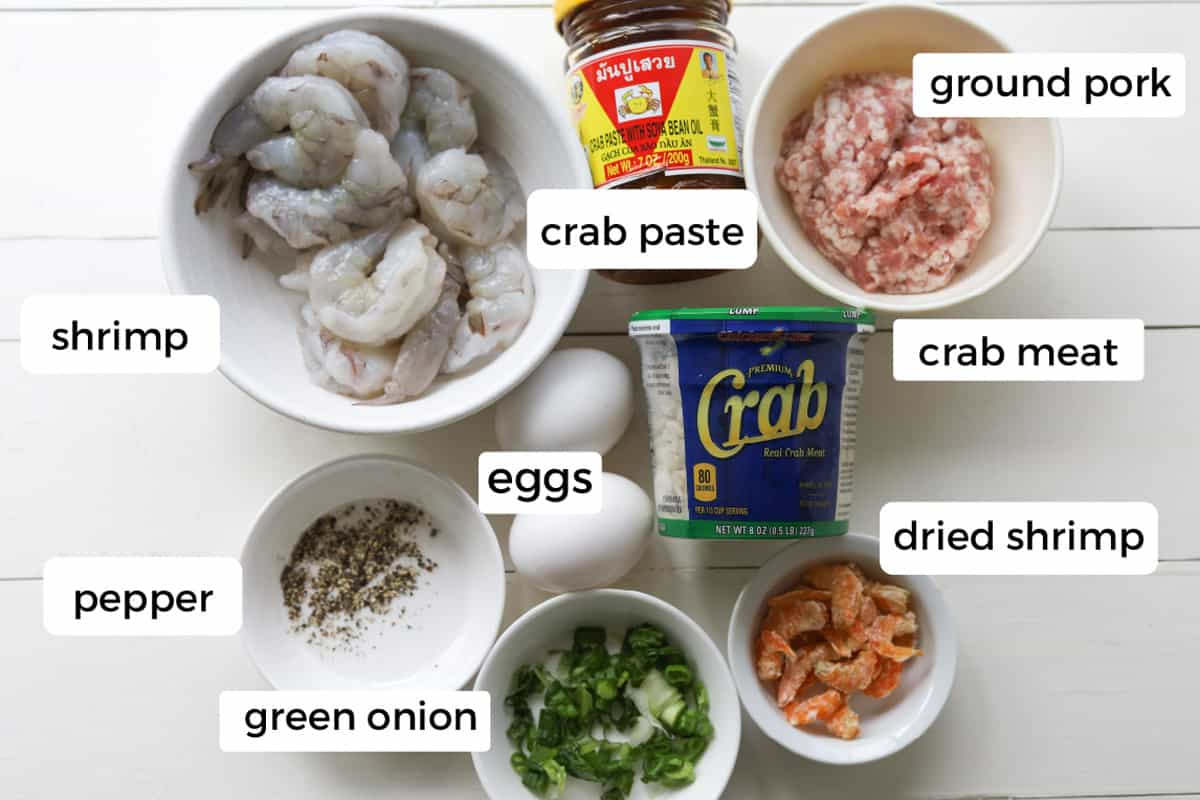 Ingredients on a table; green onion, ground pepper, dried shrimp, shrimp, eggs, crab meat, crab paste and ground pork.