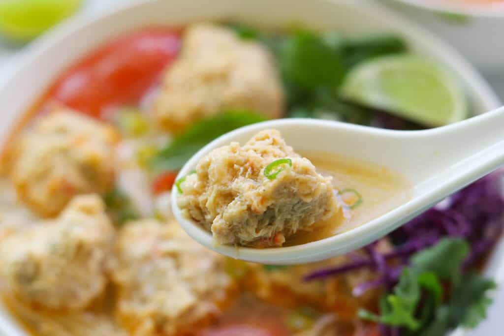 Close up picture of spoon and a bun rieu crab meatball.