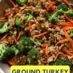 Close up of ground meat stir fry with broccoli florets and julienned carrots in a pan.