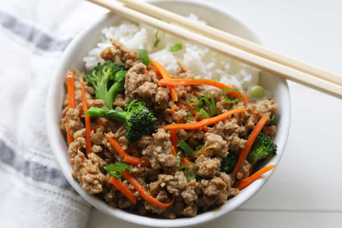 Bowl of rice with ground meat with broccoli florets and julienned carrots stirfry.
