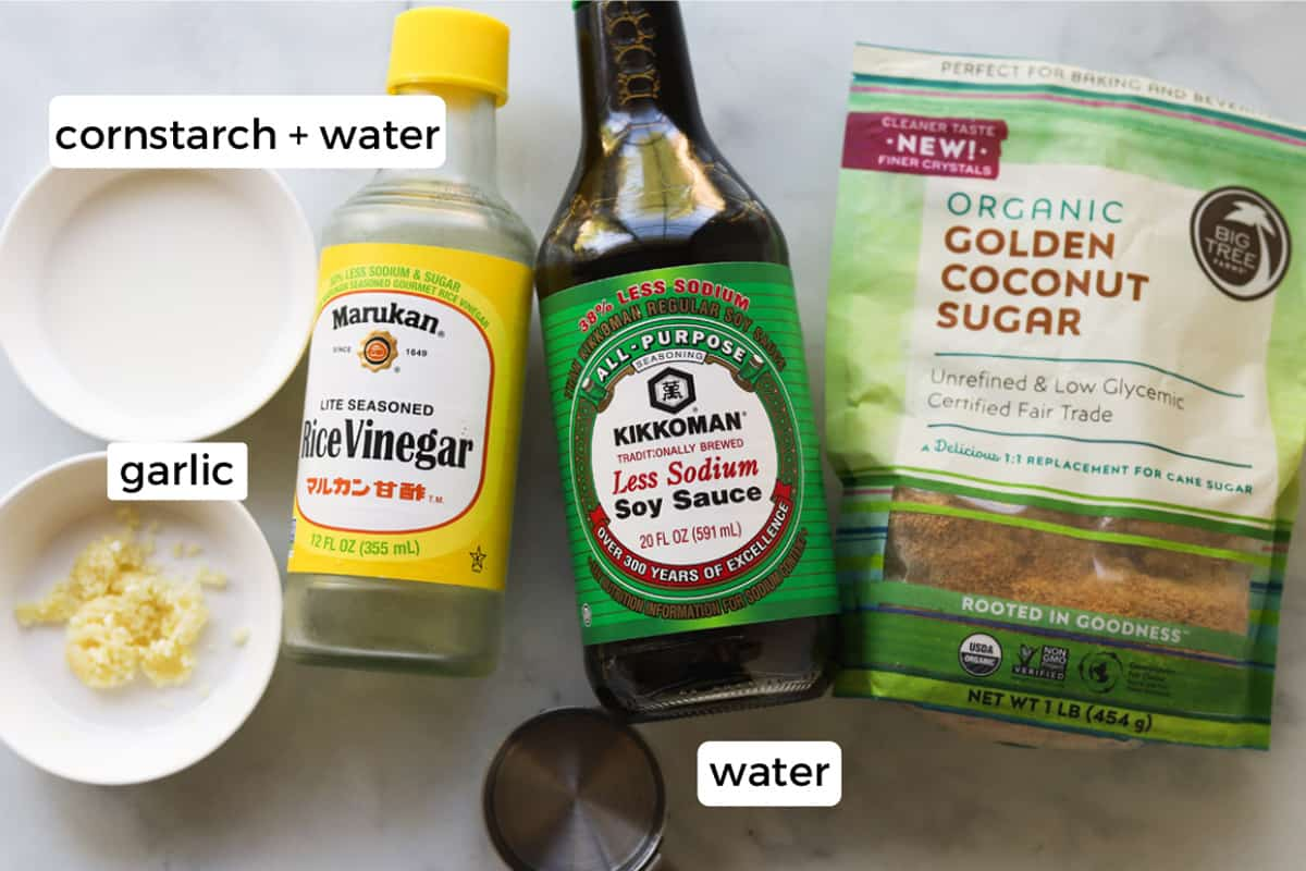 Image of ingredients on table. Cornstarch and water, minced garlic, rice vinegar, water, soy sauce and coconut sugar.