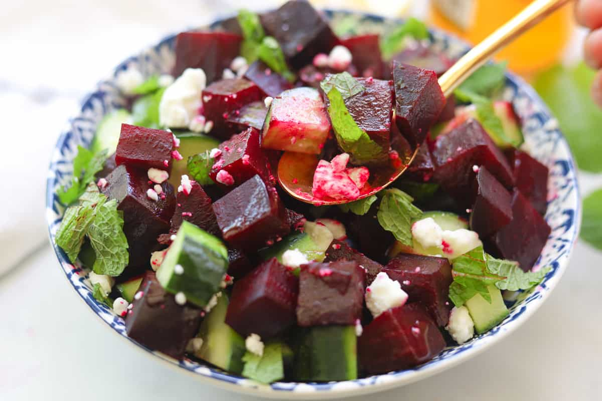 Beets and cucumber salad topped with feta crumbles and mint leaves.