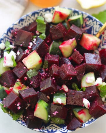 Red beet and cucumber salad bowl topped with feta and mint leaves.