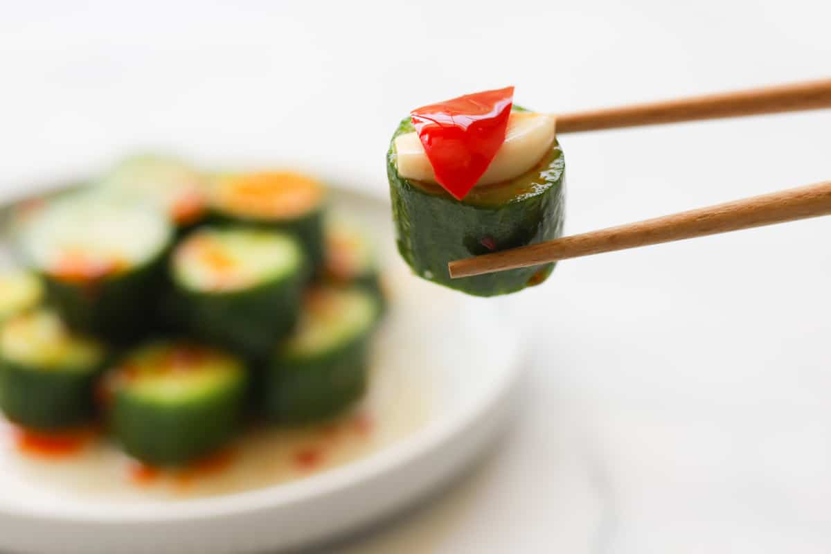 Closeup image of chopsticks holding one sliced cucumber with garlic and pepper garnish.