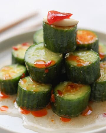 Closeup image of thickly sliced cucumbers on a dish with sauce.