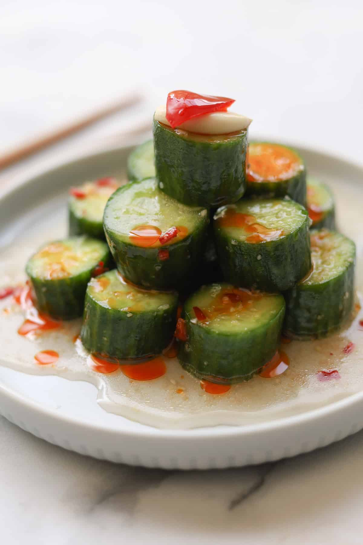 Sliced cucumbers stacked on a plate with sauce.