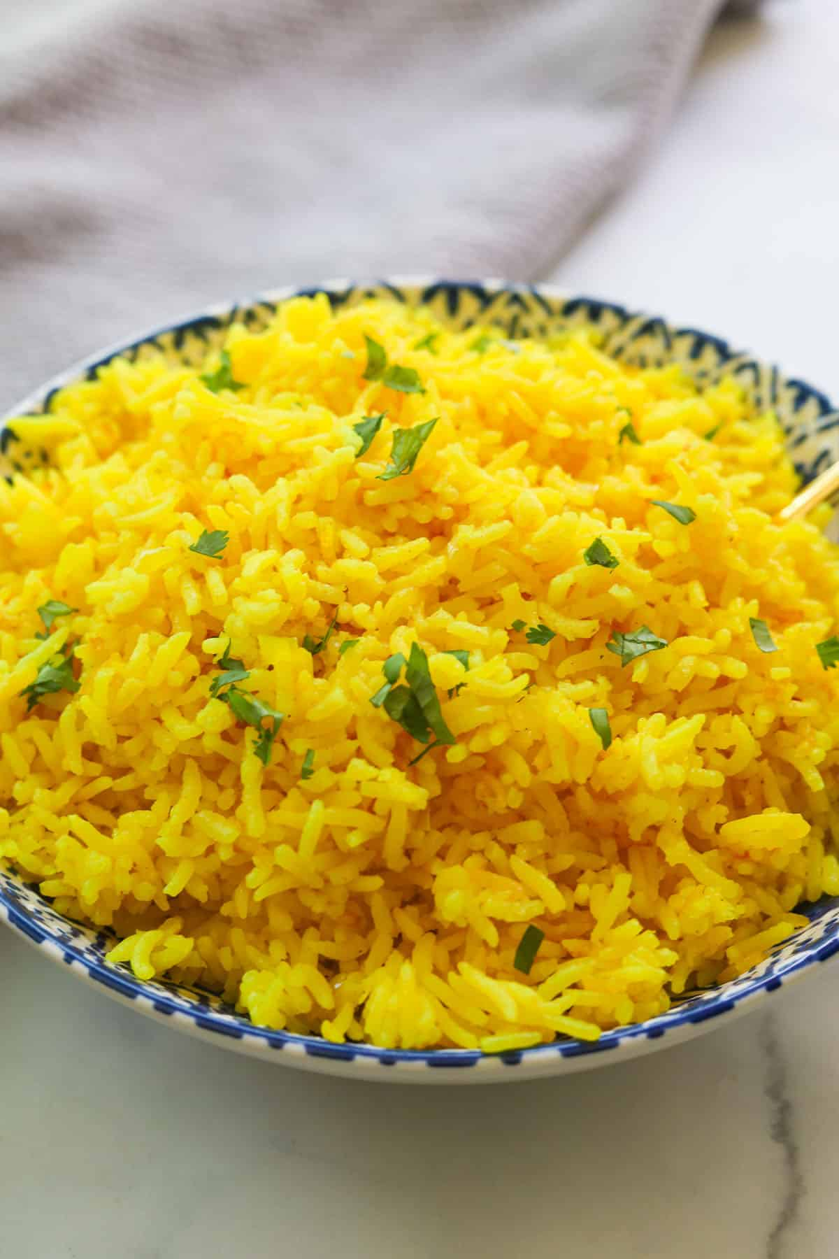 Yellow rice garnished with cilantro in a bowl.