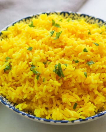 Bowl of yellow rice with cilantro leaves.