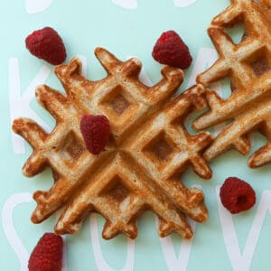 Waffles garnished with raspberries.