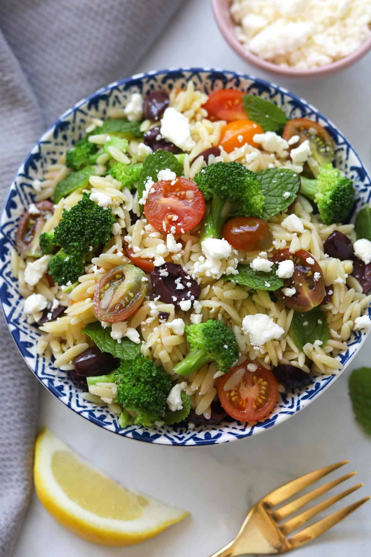 Bowl of orzo pasta salad with broccoli, tomatoes, mint leaves, olives and feta cheese.