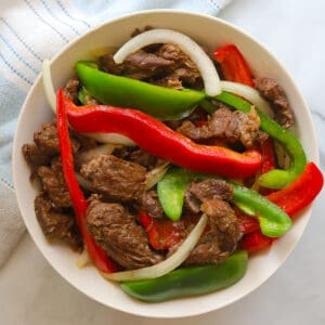 Beef stir fry with bell peppers in a bowl.