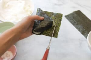 Scissors cutting onigiri seaweed piece.