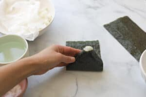 Folding onigiri triangle onto seaweed.