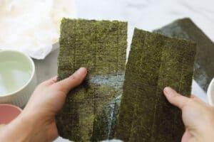 Tearing sheet of seaweed paper in half.