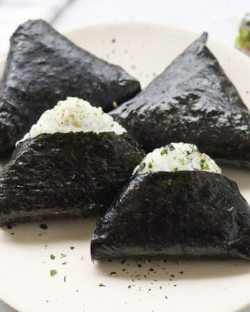 Four triangle shaped rice balls wrapped in seaweed on a plate.