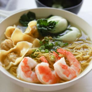 Egg noodles, wontons, shrimp and vegetable with soup in a bowl.