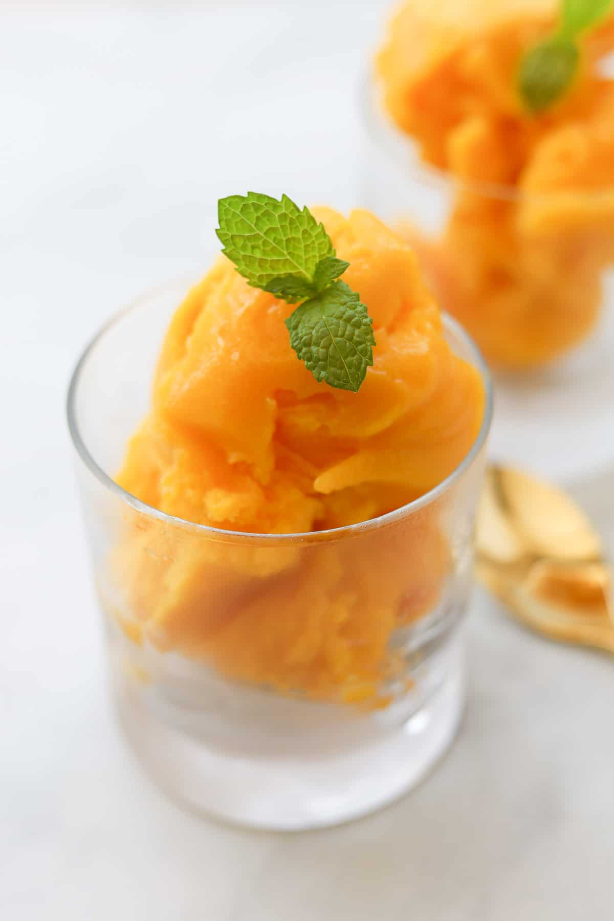 Mango sorbet garnished with mint leaves in a cup.
