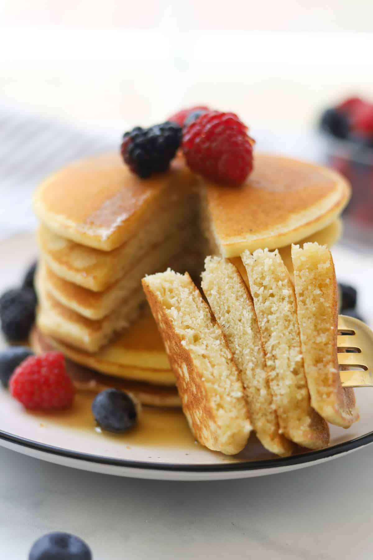 Closeup image of cut pancakes on a fork.